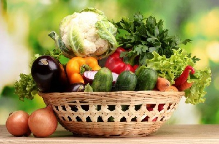 10754080-fresh-vegetables-in-basket-on-wooden-table-on-green-background Baskets For Fruits And Vegetables In Your Kitchen