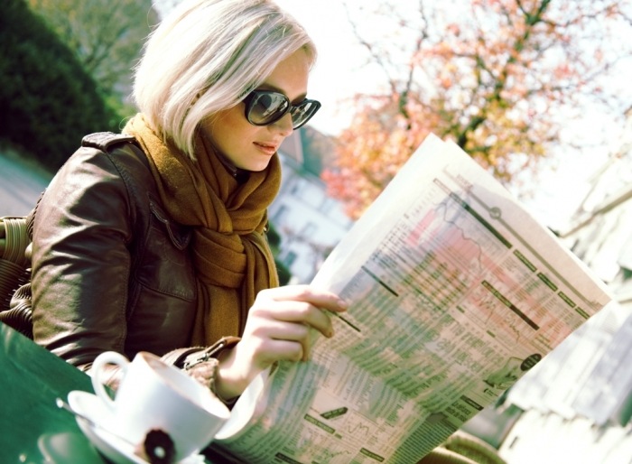 girl-with-newspaper Top 10 Trends in the Newspaper Industry