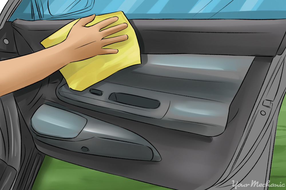 1x-How-to-Clean-Your-Car-with-Home-Ingredients-close-up-of-a-person-using-a-cloth-to-clean-the-inside-door-of-a-car 5 Common Car Smells.. and How to Remove Them?