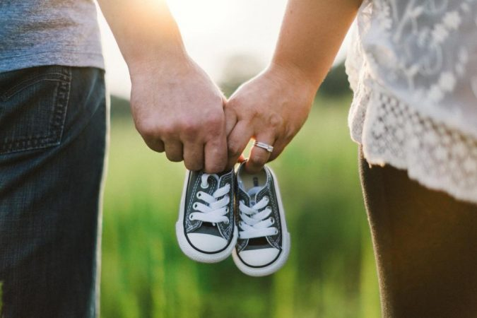 a-mom-and-dad-holding-baby-shoes-675x450 Facing Infertility Feelings: Choosing Frozen Donor Egg IVF