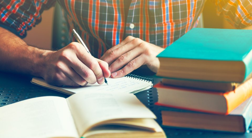 essay-writing-behind-a-pile-of-books 14 Ways to Improve Your Grades if You're Underperforming