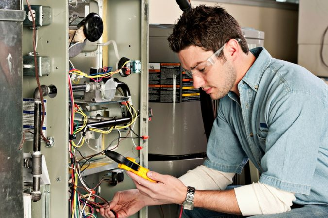 furnace-Technician-heating-wiring-675x449 Is a DIY Furnace Repair a Good Idea?