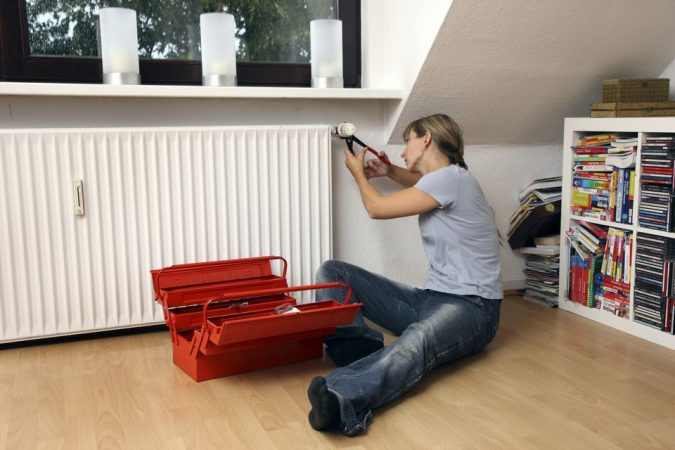 young-woman-repairing-the-thermostat-of-a-radiator-675x450 7 Most Common Furnace & heating Problems