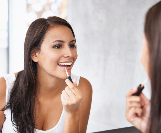 woman-applying-lip-gloss-675x558 7 Tricks to Keep Your Lipstick Last Longer