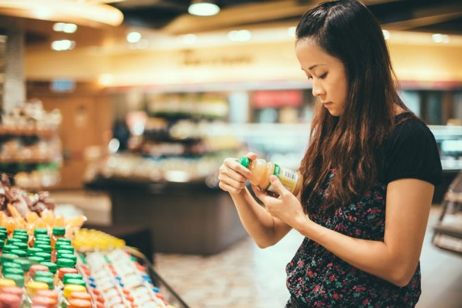 shopping-woman-reading-nutrition-label-Getty-675x450 10 Things to Consider Before Buying Food for Your Family
