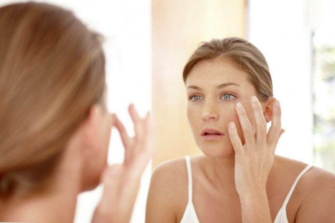 woman-looking-at-mirror-675x450 Easiest 7 Ways to Get Rid of Beauty Marks