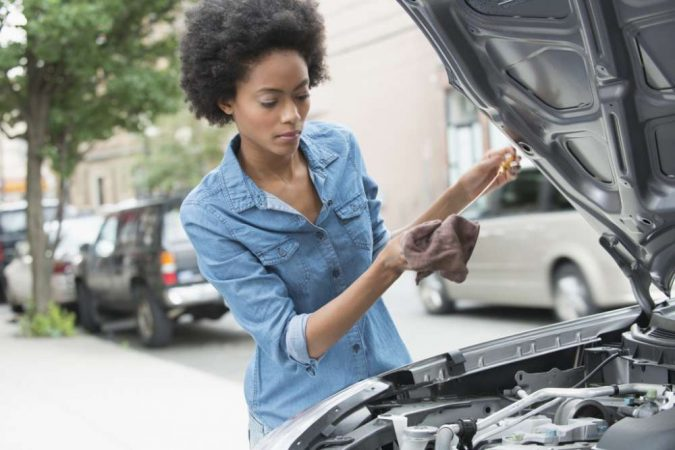 woman-checking-car-675x450 10 Essential Car Maintenance Tips That You Should Know