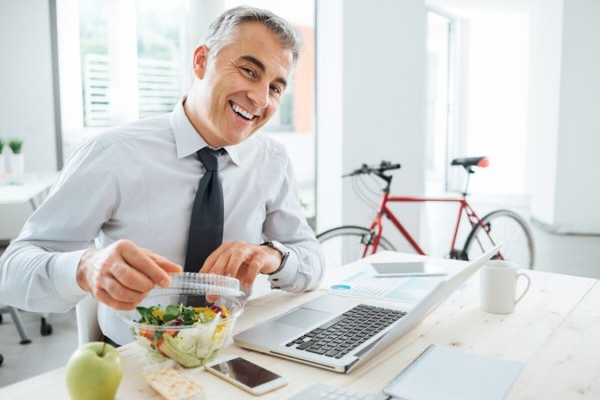 healthy-man-eating-lunch-at-work-675x450 6 Ways to Stay Healthy on a Busy Schedule