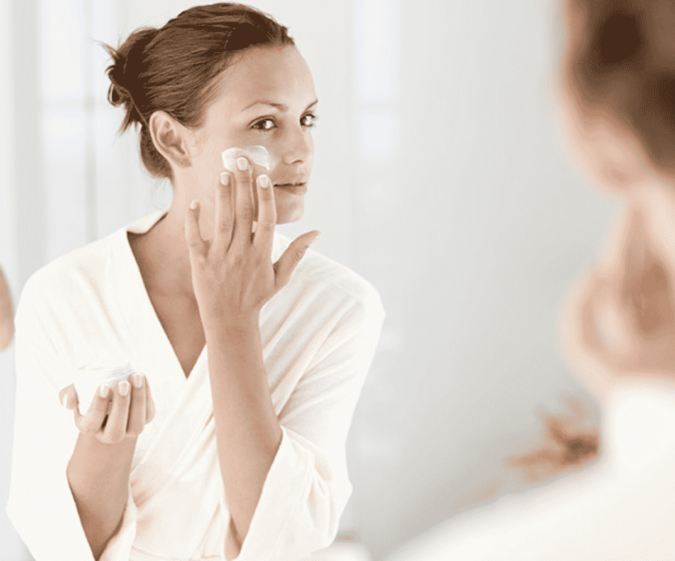 woman-moisturizing-her-face-675x561 Protect Your Skin from Acne Caused by Face Mask with Simple Remedies